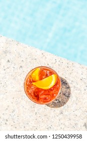 Negroni cocktail  near a pool at the resort bar or suite patio. Luxury resort, vacation, room service concept. Overhead shot. Vertical