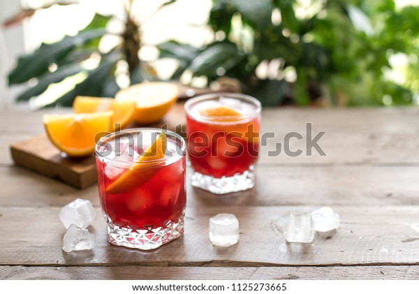 Negroni Cocktail with orange and ice. Homemade Classic Negroni cocktail and ingredients on wooden table, copy space.
