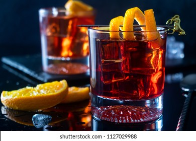 Negroni Cocktail with Orange Twist and Pin, on Dark Background. Beverage Photography.