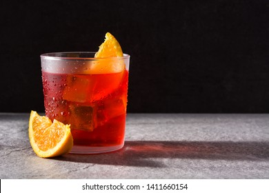 Negroni cocktail with piece of orange in glass on black background