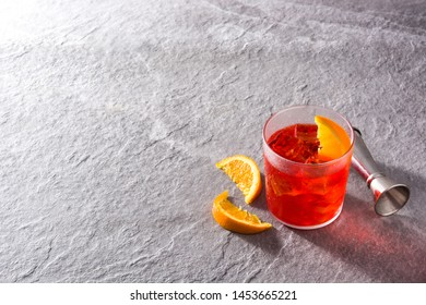 Negroni cocktail with piece of orange in glass on gray background. Copyspace