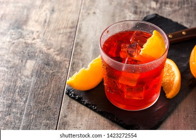 Negroni cocktail with piece of orange on wooden table