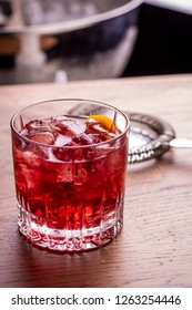 Negroni make with gin, martini red, campari bitter, served in a rock glass and garnished with orange peel
