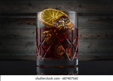Negroni make with gin, martini red, campari bitter, served in a rock glass and garnished with orange wheel