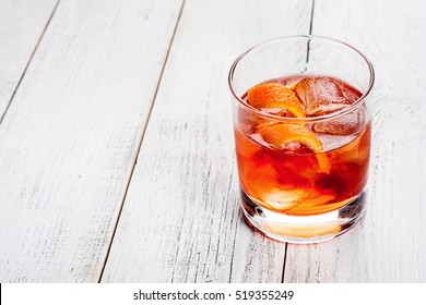 Negroni on a wooden board, white background.