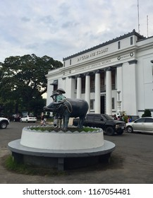 Negros Oriental, Philippines; August 24, 2018: Statue of a farmer and his carabao, a water buffalo widely used for farming, set outside the provincial capitol building in Dumaguete City.