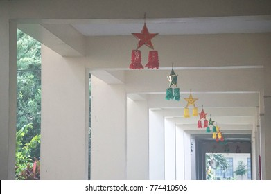 """Negros Oriental, Philippines; December 9, 2017: Star-shaped Christmas lanterns, locally known as """"parols"""", hang from the ceiling of a corridor in a school building in Silliman University."""
