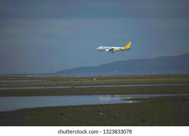 Negros Oriental, Philippines; February 5, 2019: A Cebu Pacific passenger plane flies low in its tricky approach to the Sibulan Airport runway, which starts just meters from the coastline.