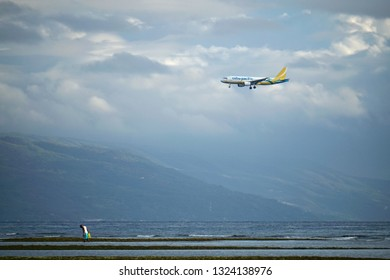 Negros Oriental, Philippines; February 5, 2019: A Cebu Pacific passenger plane descends on a tricky approach to the Sibulan Airport runway, which starts just meters from the coastline.