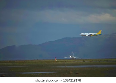Negros Oriental, Philippines; February 5, 2019: A Cebu Pacific passenger plane flies low in its tricky approach to the Sibulan Airport runway, passing over a fishing boat and man standing.