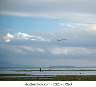 Negros Oriental, Philippines; February 5, 2019: A Cebu Pacific passenger plane starts it descent to approach Sibulan Airport, which has a runway that starts just meters from the coastline.