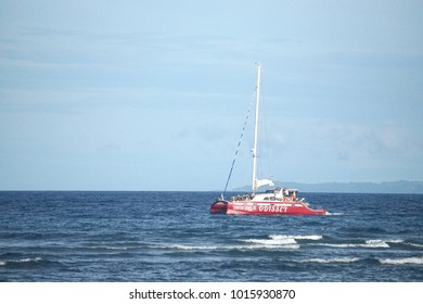 Negros Oriental, Philippines; January 6, 2018: A red yacht traverses the sea between Negros and Siquijor Islands heading towards Tanon Strait.