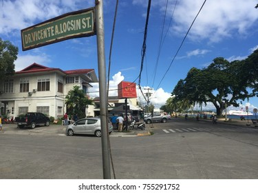 Negros Oriental, Philippines; November 14, 2017: Rusty street sign at the corner of Dr. V. Locsin Street and the Dumaguete City Boulevard.