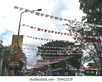 Negros Oriental, Philippines; November 18, 2017: Small flags hang above the streets whenever the city or town feast day, or fiesta, approaches.