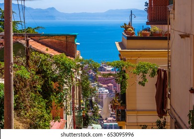 The neighborhood called Quartieri Spagnoli in Naples, Italy. Street view of old town. Narrow street of Napoli. Bright sunny day. Gulf of Naples, blue sky, sea on background. Cacti on the terrace.