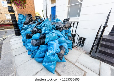 Neighborhood district of Pimlico with street, many blue pile heap of plastic color trash bags on road in London, UK, United Kingdom
