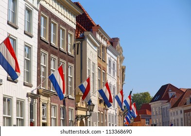 neighborhood in a dutch village with the dutch flag on queensday