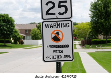 Neighborhood watch sign in a sunny Midwest suburb.