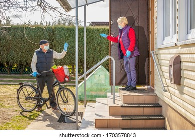 Neighborly help during coronavirus covid 19. Food delivery. Older man did shopping for an older neighbor. Man in mask stands by the old classic bicycle with a shopping bag and waving to the neighbor.