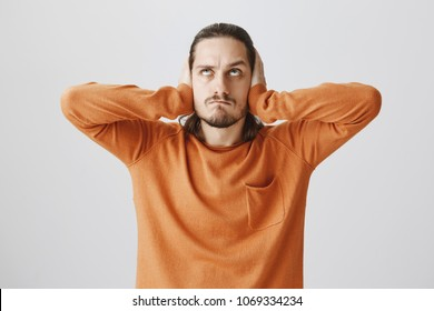 Neighbors arranged loud party. Portrait of angry annoyed young man with beard, holding up, covering ears with palms, being in rage from hearing disturbing noise from upstairs, standing over gray wall