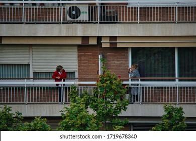 Neighbors in balconies during Coronavirus Lockdown to Boost Morale. March, 2020. Barcelona,Spain. Quedate en casa hashtag