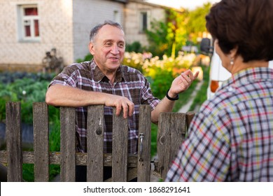 neighbors middle aged man and woman chatting near the fence in the village