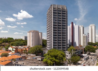 Neighbourhood of houses in green urban landscape taken over by modern high rise skyscrapers in Sao Paulo, Brazil