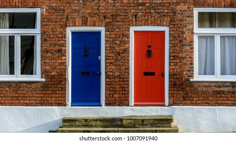 Neighbouring Terraced Houses With One Blue And One Red Front Door B, Red Brick House Facade, Shallow Depth of Field