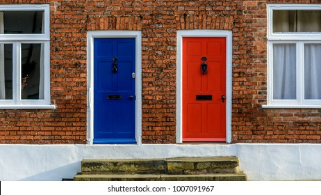 Neighbouring Terraced Houses With One Blue And One Red Front Door A, Red Brick House Facade, Shallow Depth of Field
