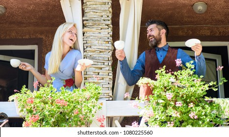 Neighbours drinks coffee at balcony and speaking. Man and woman or lovers at balcony on sunny day having good time. Neighbours lovers concept. Blonde woman and bearded man happy to see each other.