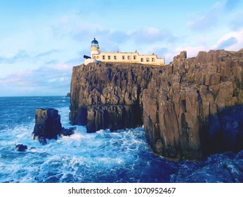 The Neist Point lighthouse on the end of  world. Foamy blue sea strikes against the sharp cliff.  The Isle of Skye, Scotland