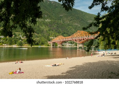 Nelson, British Columbia, Canada - August 27, 2009:  The Rotary Lakeside Park public beach on a summer afternoon and the Highway 3A bridge crossing over West Arm of Kootenay Lake.