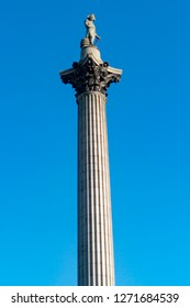 Nelson column in trafalgar square standing tall with blue sky