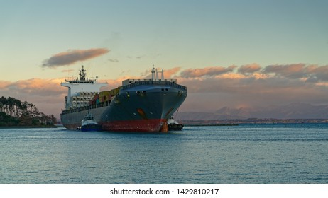 NELSON, NELSON/NEW ZEALAND - JUNE 16, 2019: [Two pilot vessels nudge a container ship through the cut and into Port Nelson, New Zealand.]