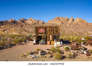 Nelson, Nevada, USA - October 23, 2018 : Old wooden garage, vintage fuel pumps and rusty car wrecks in Nelson ghost town located in the El Dorado Canyon and surrounded by Eldorado Mountains.