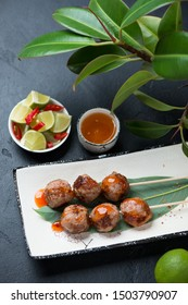 Nem nuong or fried vietnamese pork meatballs on skewers with fish sauce. Vertical shot on a black stone background