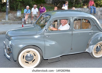 NENDAZ, SWITZERLAND - JULY 27: Proud owner of a vintage Renault in a parade at the International Alpine Horn Festival:  July  27, 2013 in Nendaz, Switzerland