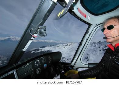 NENDAZ, SWITZERLAND - MARCH 15: Helicopter pilot flying the helicopter used for filming the Nendaz Freeride Finals: March 15, 2014 in Nendaz, Switzerland