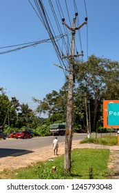 NENMENI, KERALA, INDIA - OCTOBER 24, 2018: A utility pole supporting a mass of wiring, some haphazard, in the town of Nenmeni in Kerala, in southern India.