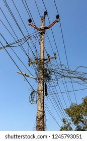 NENMENI, KERALA, INDIA - OCTOBER 24, 2018: A utility pole supporting a mass of wiring, some haphazard, in an Indian town in the southern state of Kerala.