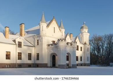 Neo gothic Alatskivi castle at winter. White building and white snow around.