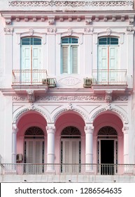 Neoclassical architecture with column in pale rose with white door and pillars in Vedado Havana in Cuba
