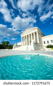 Neoclassical columned entrance portico to the US Supreme Court building in Washington DC with fountain in the foreground.