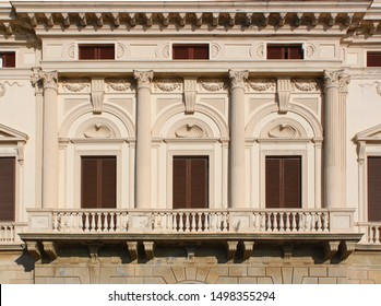Neoclassical palace facade detail with closed windows, balcony and corinthian columns in Livorno, Italy