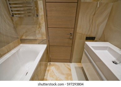 A neoclassical-style bathroom with marble tiles on walls and floors, a bath, a washbasin and a toilet, stock photo