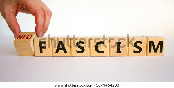 Neofascism symbol. Man hand turns a cube and changes the word fascism to neofascism. Business and fascism or neofascism concept. Beautiful white background, copy space.