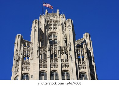 Neo-gothic architecture on Chicago Tribune Building, framed with clear blue sky