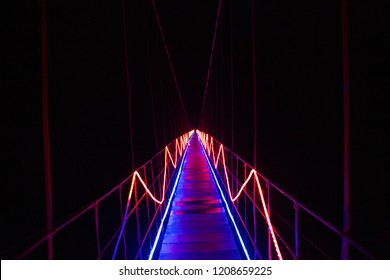A neon bridge leads to empty darkness. Road leading to unknown mystery. Pathway to discovery and emptiness.