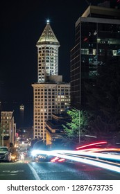 Neon Car Streaks on Seattle Streets with Lit Tower and Puget Sound at Night