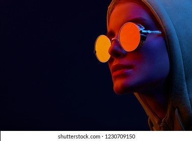 Neon close up portrait of young woman in round sunglasses and hoodie. Studio shot